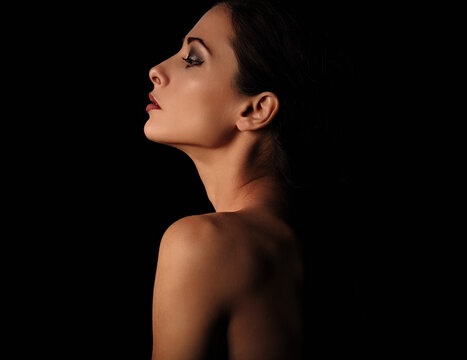 Beautiful mysterious woman in darkness with healthy neck, shoulders and serious wisdom look on dramatic  black background with empty copy space. Closeup portrait. Profile view.