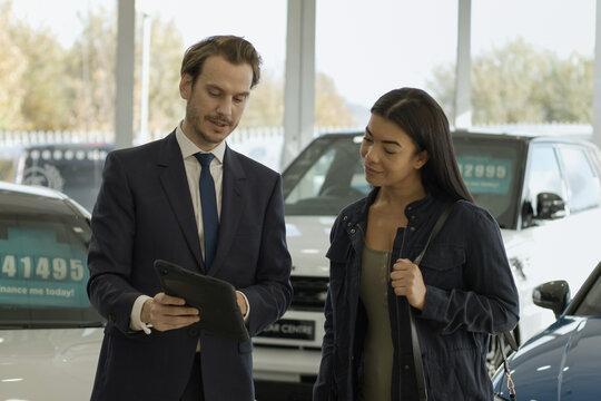 Car sales person talking to customer in car dealership showroom, looking at digital tablet