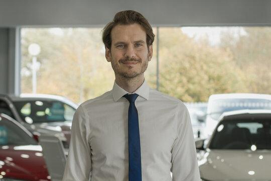 Portrait of car salesman in showroom