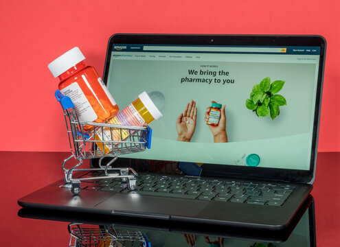 Morgantown, WV - 18 November 2020: Minature shopping cart holding prescription drugs in front of screen with Amazon Pharmacy landing page