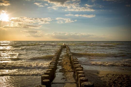 Eine Buhne ragt in die Ostsee während des Sonnenuntergangs
