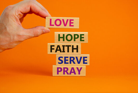 Positive single word list on wooden blocks with words 'pray, serve, faith, hope, love'. Male hand. Beautiful orange background, copy space. Concept.