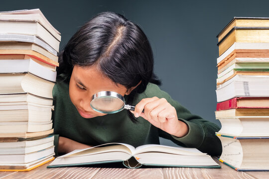 Child Use Magnifier on Opened Book