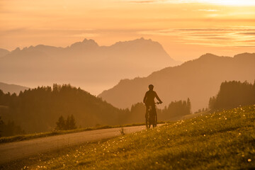 active woman riding her electric mountain bike at sunset in front of the awesome silhouette of Mount Saentis, Appenzell switzerland