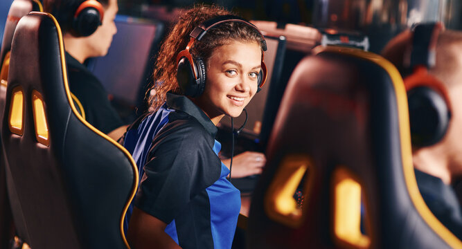 Portrait of a young happy mixed race girl, female gamer wearing headphones smiling at camera while playing online video games, participating in eSport tournament