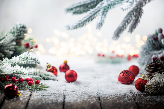 Christmas red decorations on snow with fir tree branches and christmas lights. Winter Decoration Background with copy space for text
