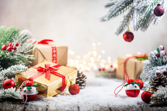Christmas red decorations on snow with gift boxes, fir tree branches and christmas lights. Winter Decoration Background with copy space for text