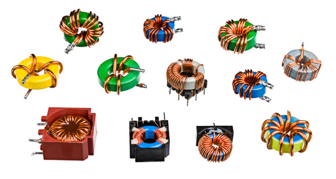 Various toroidal inductors and transformers isolated on a white background. Collection of electronic induction coils in toroid shape with wrapped copper wire on ferromagnetic core. Electrotechnology.