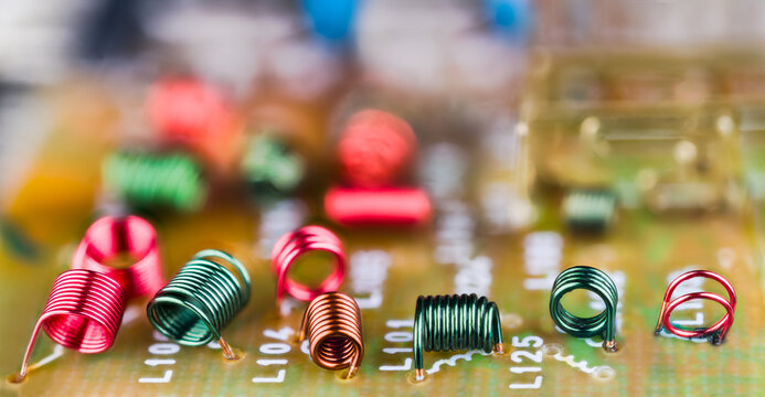 Electromagnetic air-core inductors for high frequencies on circuit board panoramic background. Electronic coils inside detail of TV device for receiving radio-frequency signal. Selective focus. Bokeh.