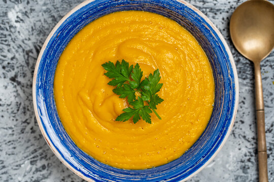 Roasted pumpkin and carrot soup with cream and pumpkin seeds in bowl background