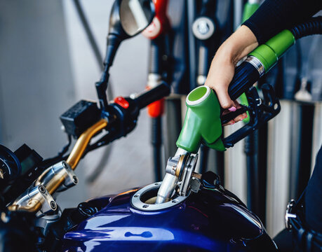 Flammable production. A storage of gas and motorbike this is filling with fuel. A hand of human is holding a green pistol.