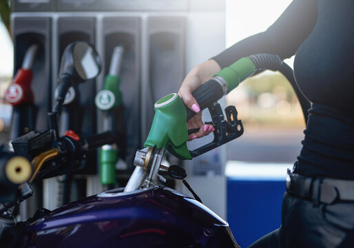 Female's gentle hand is holding a fueling gun. Motorcycle's tank is fueling by female owner.