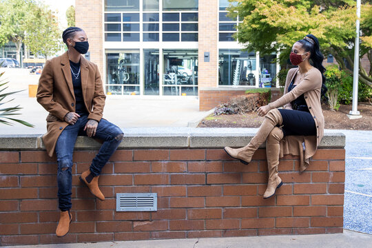 Two African American women wearing masks to protect from the Covid-19 coronavirus sit 6 feet apart for social distancing while talking