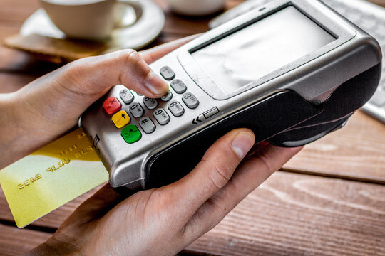 Payment by card in cafe with terminal and keyboard on wooden background