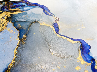 Abstract blue background with beautiful smudges and stains made with alcohol ink and gold pigment. Fragment of art with blue texture resembles watercolor or aquarelle painting.