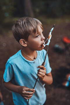 Portrait of cheerful youth boy eating marshmallow on a stick in summer relaxed forest.