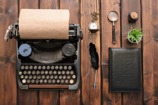 Black leather book, typewriter, magnifying glass, pocket watch and quill pen on the brown wooden desk table background.