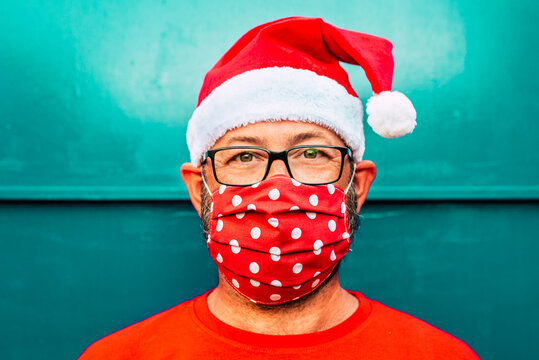 Portrait of adult caucasian man wearing red protection mask for coronavirus covid-19 and santa claus chrismtas hat - concept of people alone during holidays and virus emergency