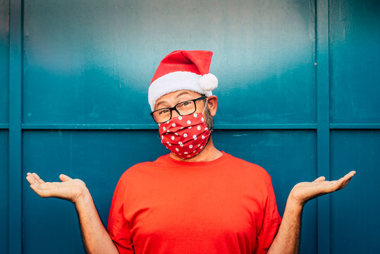 Portrait of cheerful and desolated adult man with red santa hat and face mask for coronavirus covid-19 virus emergency - concept of christmas and holidays alone during lockdown