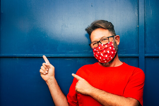 Portrait of cheerful man with red face protection mask for covid-19 coronavirus emergency with copy space on blue nackground - people and outbreak for virus war and health care
