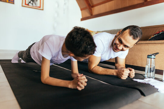 Young father and child son training and stretching at home