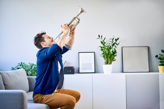 Man sitting on couch playing trumpet