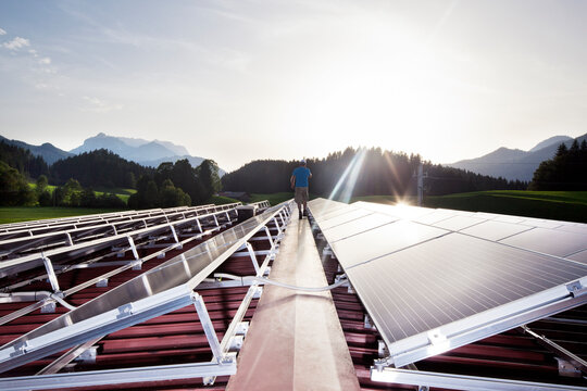 Austria, Tyrol, Koessen, back view of worker walking on solar plant in the evening