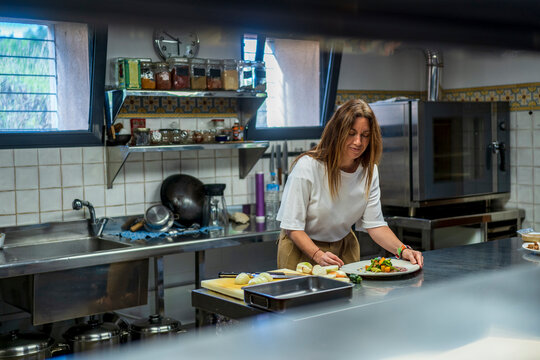 Confident female dietitian preparing meal at commercial kitchen