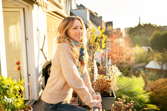 Portrait of smiling blond mature woman standing on balcony at autumn