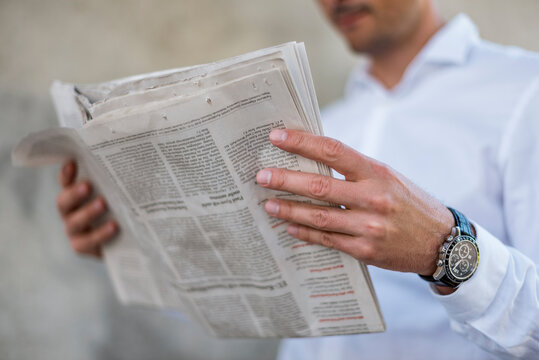 Close-up of businessman reading newspaper