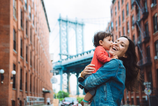 USA, New York, New York City, Baby kissing mother in Brooklyn with Manhattan Bridge in the background