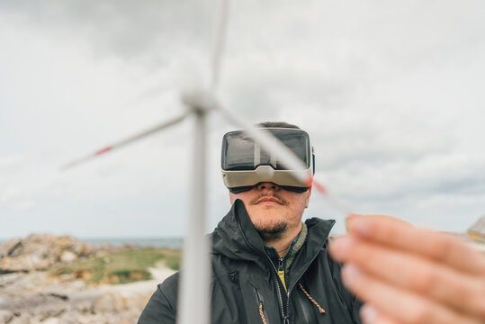 France, Brittany, Meneham, man with miniature wind turbine wearing VR glasses at the coast