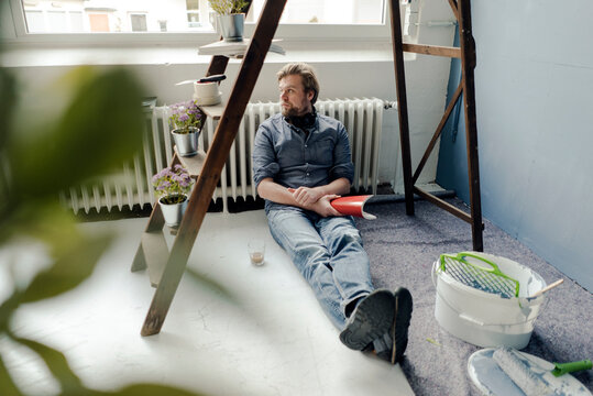 Man renovating room sitting on the floor having a rest