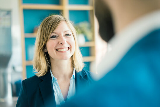 Businesswoman smiling at businessman in office