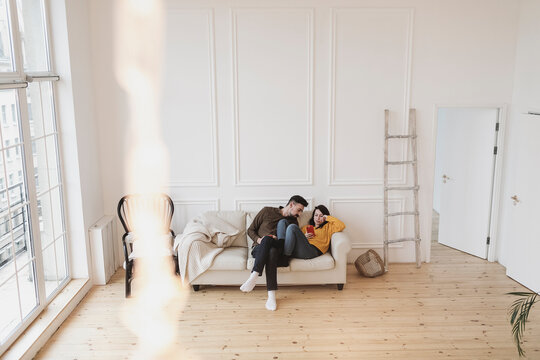 Couple sitting on the couch in the living room of new home looking at cell phone