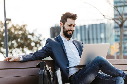 Businessman sitting on bench outside office building using laptop