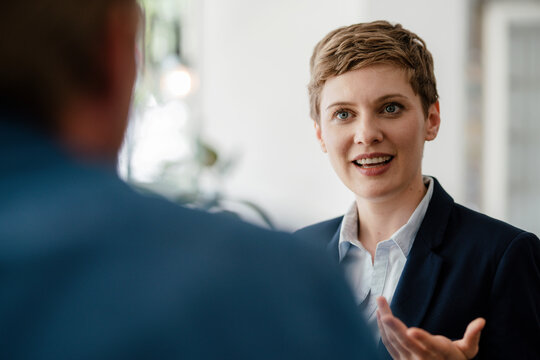 Portrait of businesswoman talking to a colleague