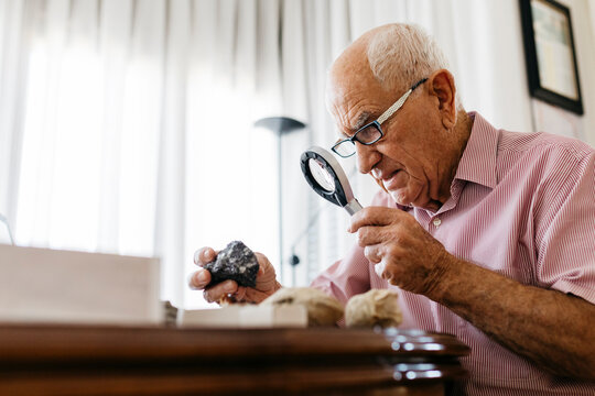 Retired senior male using magnifying glass for research of fossil and mineral at home