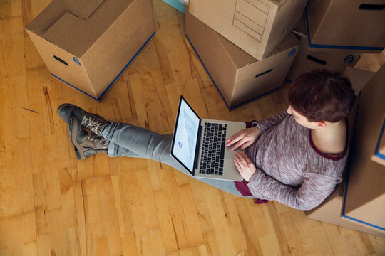Woman using laptop with rising line graph on the screen in a new home