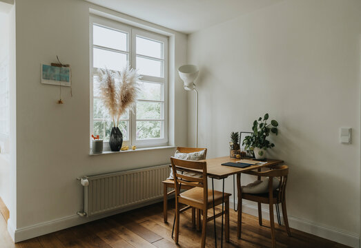 Modern interior of room with table and chairs by window at old house