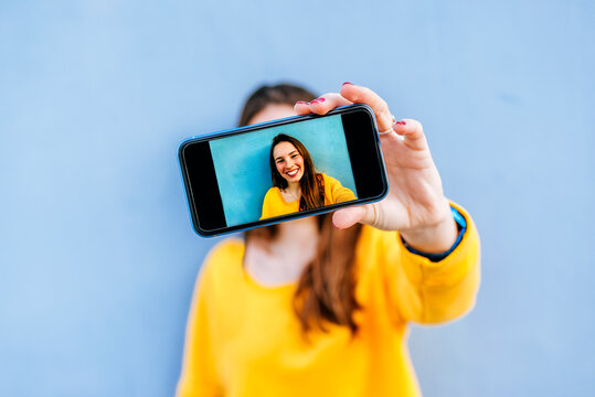 Smiling young woman taking a selfie at a blue wall