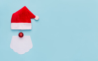 Santa Claus Christmas concept. Overhead above close up view photo of funky bright color hat white beard and tree toy as a nose isolated over pastel blue background