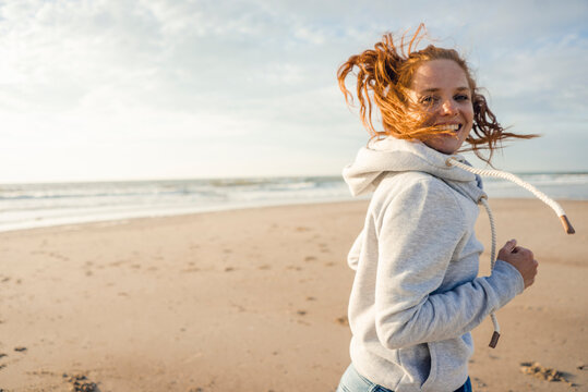Redheaded woman running on the beach, laughing