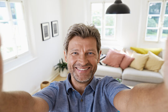 Mature man at home taking a selfie