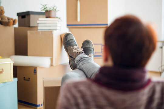 Woman relaxing surrounded by cardboard boxes in a new home