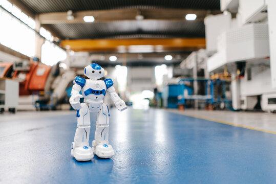 Toy robot standing on floor of factory workshop