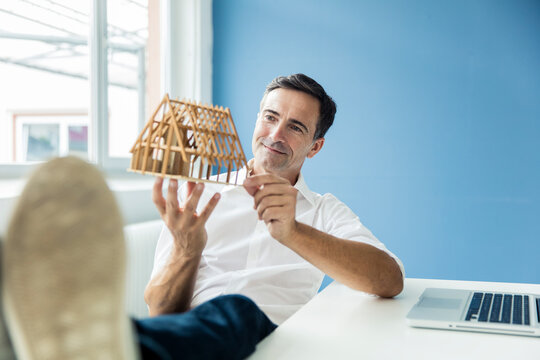 Confident businessman looking at model house in office