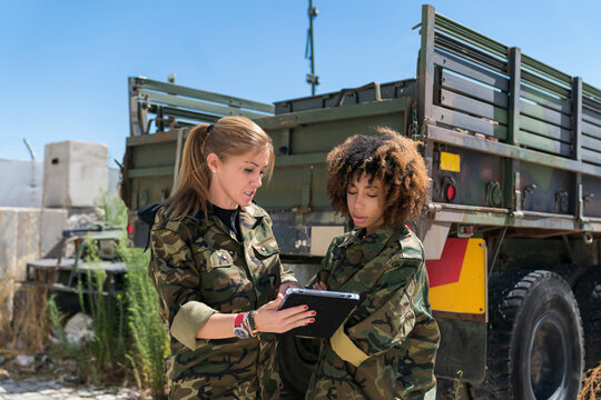 Multi-ethnic female army soldiers discussing over digital tablet at military base on sunny day