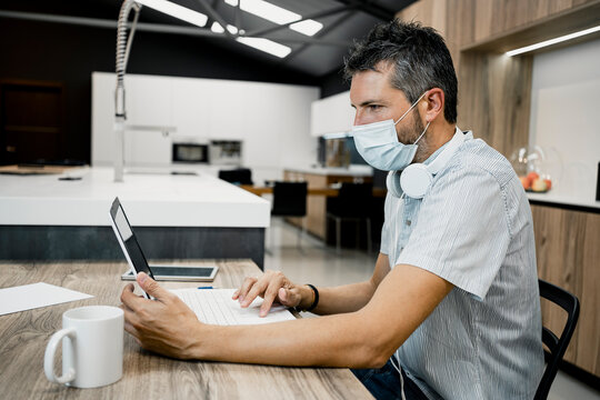 Businessman wearing protective mask while using laptop at desk in office during COVID-19 pandemic