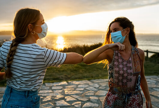 Women in protective face masks elbow bumping against sky during COVID-19 outbreak